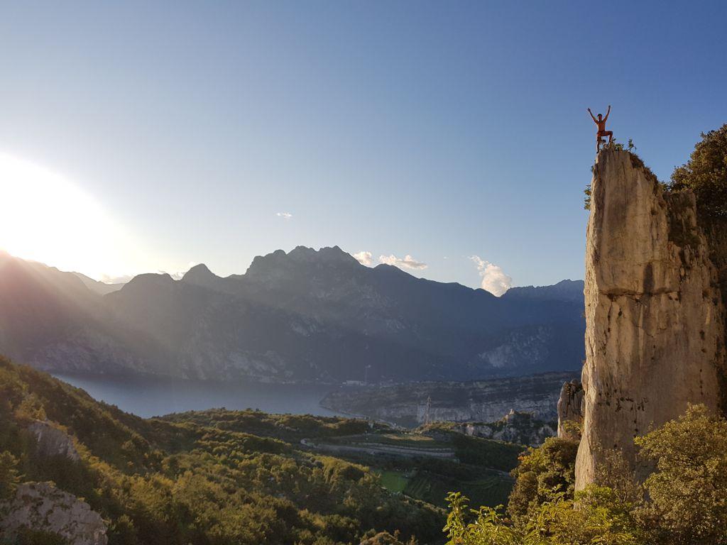 Kletterer auf Felsturm in Arco mit Sicht auf dden Gardasee