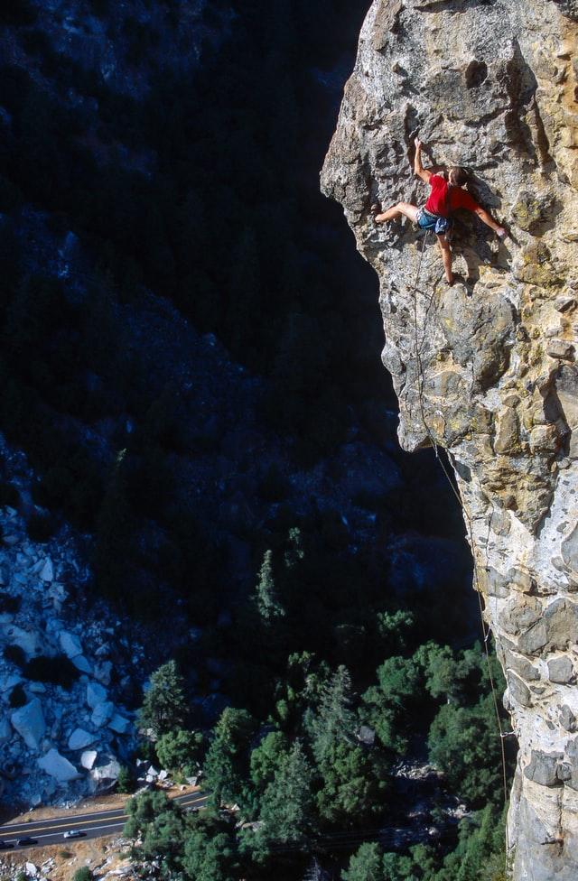 Kletterer an ausgesetzter Kante am Fels